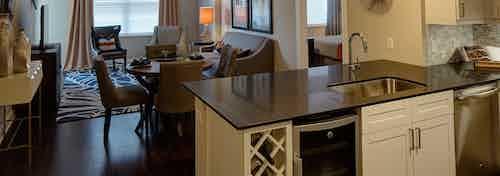 AMLI Deerfield open floorplan kitchen and living room featuring large dark countertop island and beverage refrigerator