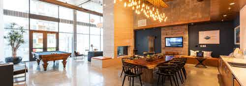 Interior of poolside clubhouse with stylish lounge seating and wood paneling wall with big screen TV at AMLI Marina Del Rey