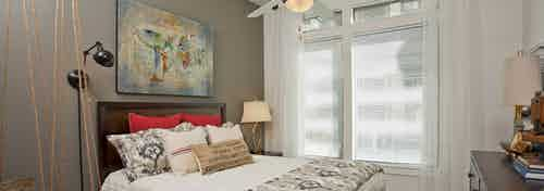 Bedroom at AMLI 5350 with a white bed against a dark grey accent wall next to a large window with sunny daytime views