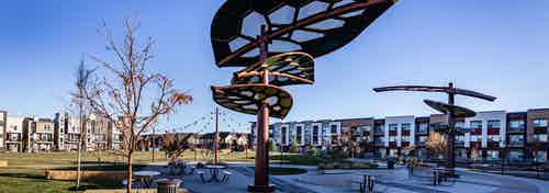 Daytime view of AMLI Littleton Village apartment building adjacent to 3.5-acre park with leaf canopies and festoon lighting