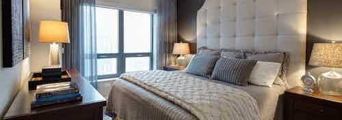 AMLI River North bedroom with natural daytime light and beige decor in front of a window with sheer curtains and a city view