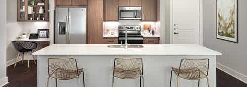 AMLI Addison kitchen with white island and quartz countertops with three barstools and a built in desk next to refrigerator