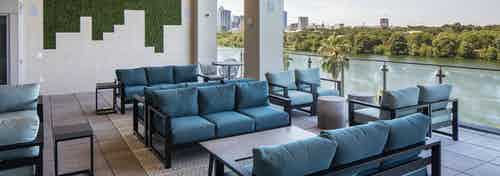 Rooftop deck at AMLI South Shore with blue cushion seating and scenic views of Lady Bird Lake and downtown Austin skyline