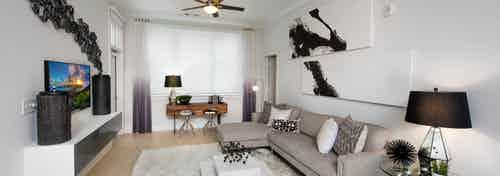 Alternate angle of AMLI Buckhead living room with black, white and beige color scheme with creme walls and light wood floors