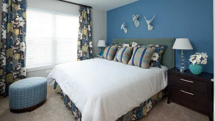 Bedroom at AMLI Evanston with blue walls and white bedding and a bright daytime view out of a window with patterned curtains