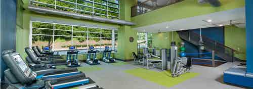 Fitness center at AMLI Piedmont Heights apartments with treadmills as well as cardio and strength machines with large windows