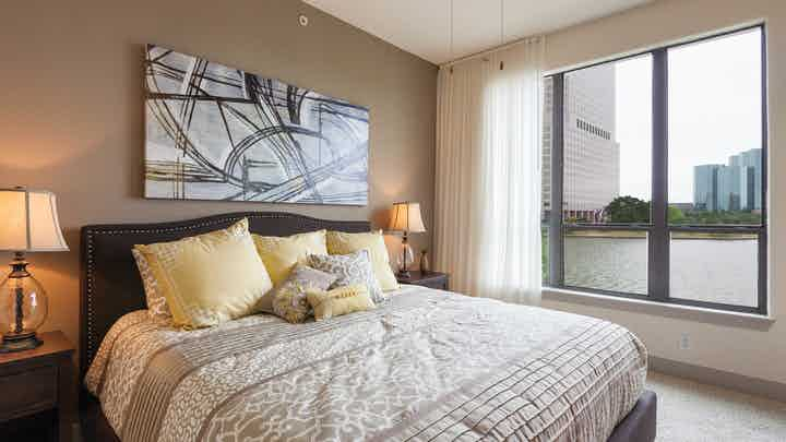 Interior view of AMLI Las Colinas apartment bedroom with bed and nightstands and large window with curtains overlooking lake