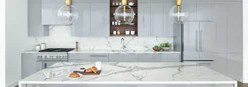 AMLI Fountain Place penthouse kitchen with gray cabinets and a white stone island with glass and gold pendant lights above