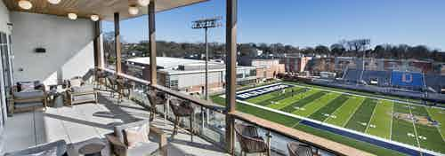Daytime view of sky lounge deck at AMLI Decatur with multiple seating areas overlooking Decatur Bulldogs football field