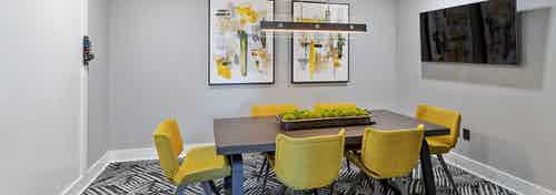 AMLI Parkside conference room with brown table and 6 mustard chairs and abstract art on the wall and hanging light fixture