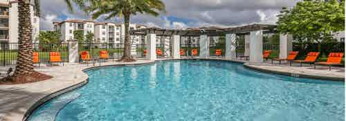 Daytime view of AMLI Doral swimming pool surrounded by bright orange lounge chairs, palm trees and freestanding pergola