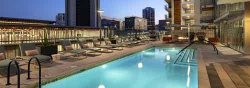 Nighttime view of AMLI Park Broadway swimming pool area with lounge seating overlooking library and Downtown Long Beach