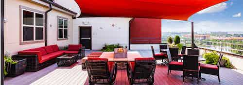 A Rooftop lounge area of AMLI Interlocken apartments with burgundy furniture and an overhead shade with west facing blue sky