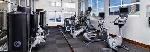 Interior of the fitness center at AMLI Park Avenue apartments with treadmills and elliptical training machines and windows
