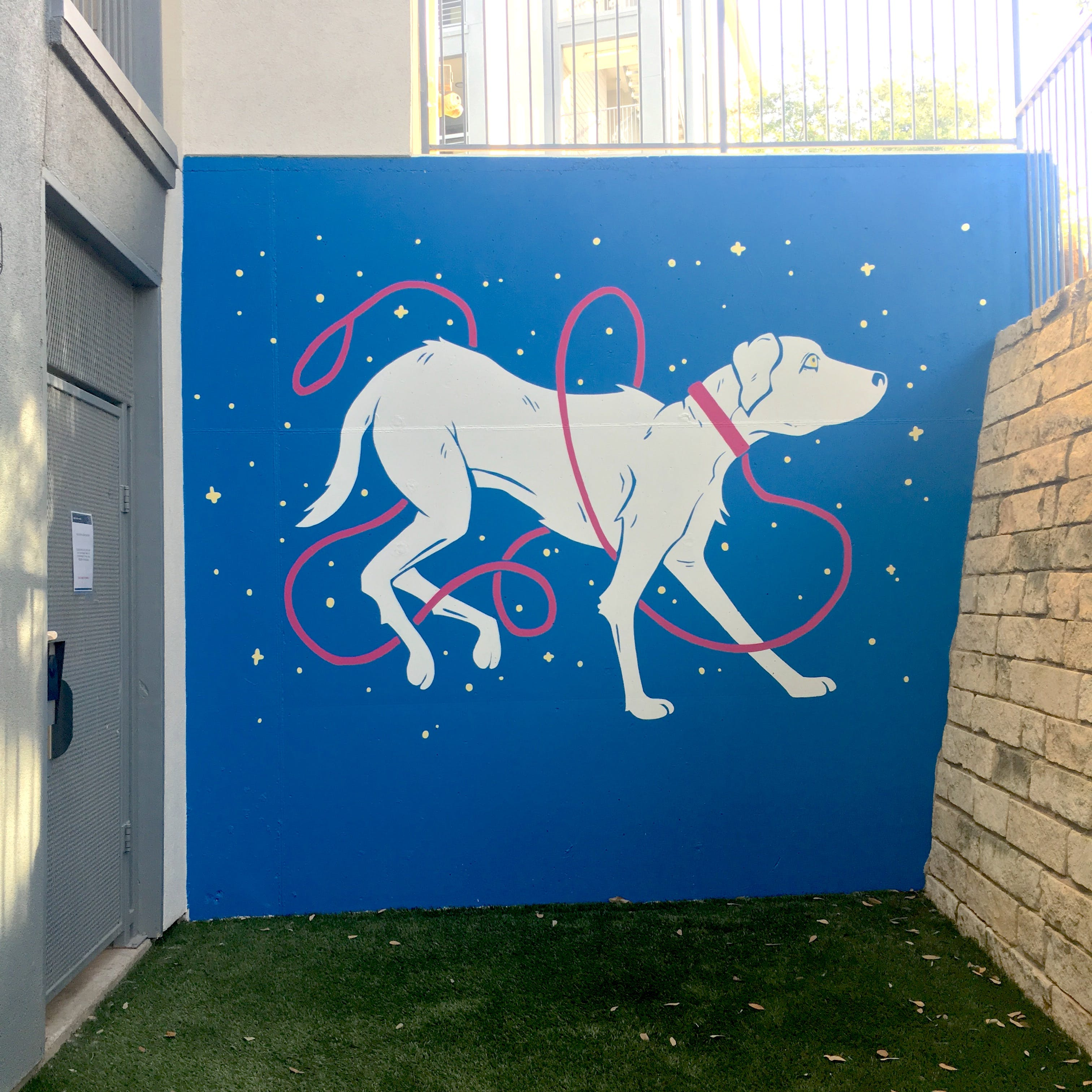 mural of a white dog on a blue wall with sparkles all around