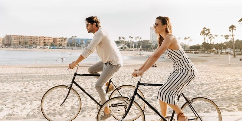 couple biking on beach
