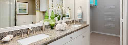 AMLI Memorial Heights apartment bathroom with granite double vanity and white cabinets and view into walk-in closet