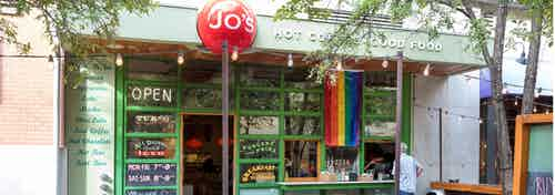 Close up of Jo's restaurant exterior on the first level of AMLI Downtown with red sign and rainbow flag hanging near entrance