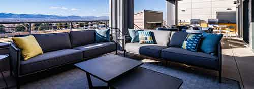 Daytime view of Rooftop outdoor lounge with fireplace, grilling station and cozy seating at AMLI Littleton Village apartments