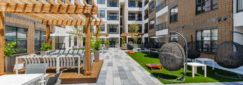 AMLI Quadrangle courtyard with wood pergolas with abundant seating and grassy areas hanging basket swing chairs