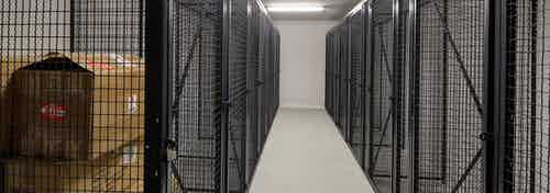 Interior view of large black storage cages on each side of the room with one containing boxes at AMLI Deerfield