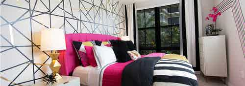 AMLI Dadeland master bedroom with geometric accent wall, modern table lamp, magenta and black bedding and a window view