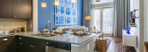 Interior of kitchen at AMLI on Riverside with spacious counter connecting to living space with tall glass balcony doors