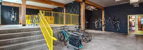 Interior bike room of AMLI Wallingford with bike storage tools storage lockers with large floor to ceiling windows facing the sidewalk