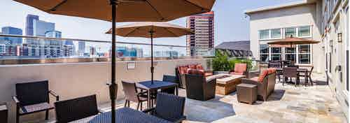 Exterior view of the sky deck at AMLI Park Avenue apartments with several tables and chairs and umbrellas and Denver skyline