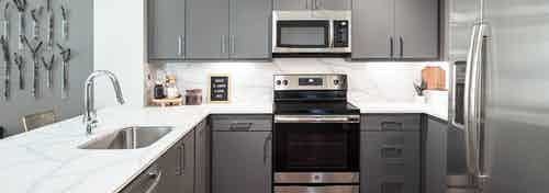Interior view of AMLI Addison kitchen with grey cabinets and quartz countertops and backsplash with peek into living area