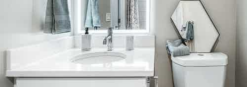 AMLI Bellevue Park apartment bathroom with back it mirror over white quartz vanity with white toilet with mirror on top