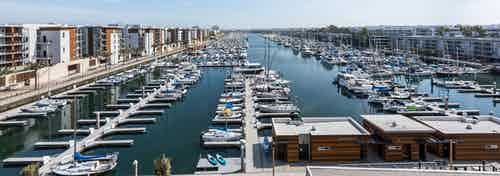Daytime aerial view of the marina, boat slips with boats and boat houses and part of AMLI Marina Del Rey apartment buildings