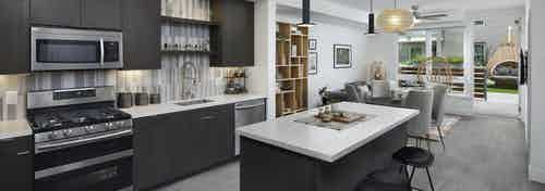 AMLI Park Broadway apartment kitchen with dark wood cabinets and light quartz countertops and furnished living room