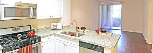 AMLI Warner Center apartment kitchen with white cabinets, stainless steel appliances and living room with hardwood floors