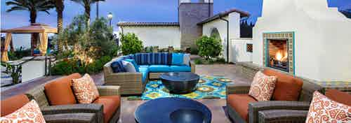 Dusk view of AMLI Spanish HIlls outdoor courtyard with fireplace, cozy and multicolored lounge seating and lush planters