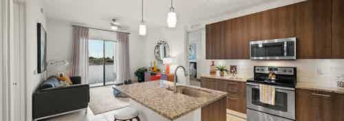 AMLI 8800 apartment with island kitchen with stools, stainless steel appliances, wood cabinetry and peek into living area