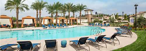 Daytime view of AMLI Spanish Hills apartment swimming pool area with plentiful lounge seating and cabanas and palm trees