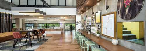 Interior view of AMLI Lenox clubhouse with multiple seating areas and wood floors and brightly colored artwork