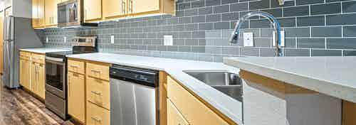 Interior view of AMLI 535 apartment with upgraded kitchen with tile back splash stainless steel appliances and quartz counter tops