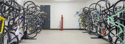 Bicycle storage room at AMLI Addison apartments with red tire pump and full black bicycle racks against two white walls