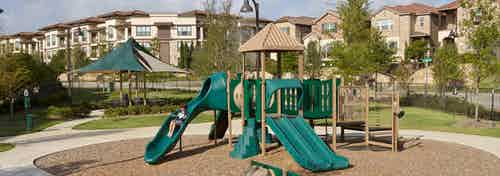 Playground with green slides on a bed of woodchips with a blue sky, trees and apartment building facade in the background