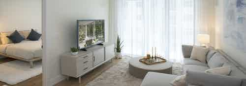 AMLI Midtown Miami apartment living room with sofa and round coffee table and TV sitting on chest and peek into bedroom