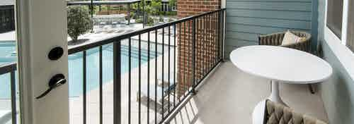 Exterior view of a balcony on one of the AMLI Decatur apartments with two chairs and a table overlooking the pool area