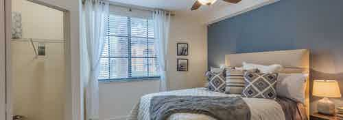 AMLI Toscana Place apartment bedroom with white and gray bedding and blue wall and open closet and window with blinds