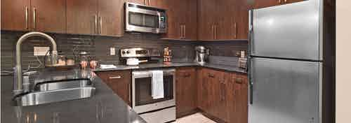 Interior view of AMLI Mark24 apartment kitchen with dark cabinets black back splash black quartz counter tops and stainless steel appliances
