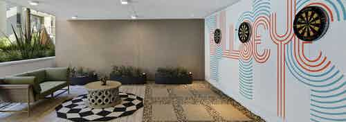 Daytime view of outdoor courtyard cave with round checkered rug and three dartboards on wall at AMLI Park Broadway apartments