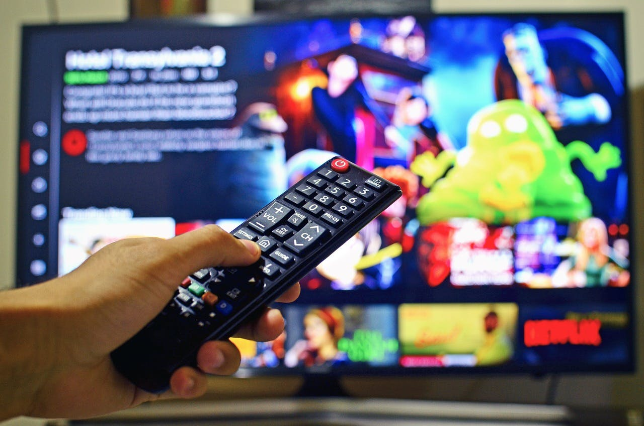 Person holding TV remote in the foreground with Netflix on the TV in the background
