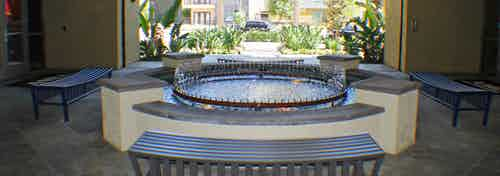 Exterior daytime view of AMLI Warner Center apartment wishing well-style fountain with surrounding benches and lush greenery