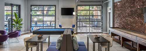 Resident game room at AMLI Eastside apartments with a pool table and shuffleboard surrounded by colorful seating