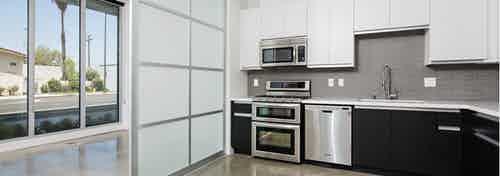 Interior of AMLI Lex on Orange apartment kitchen with quartz countertops, white cabinetry and frosted glass sliding door
